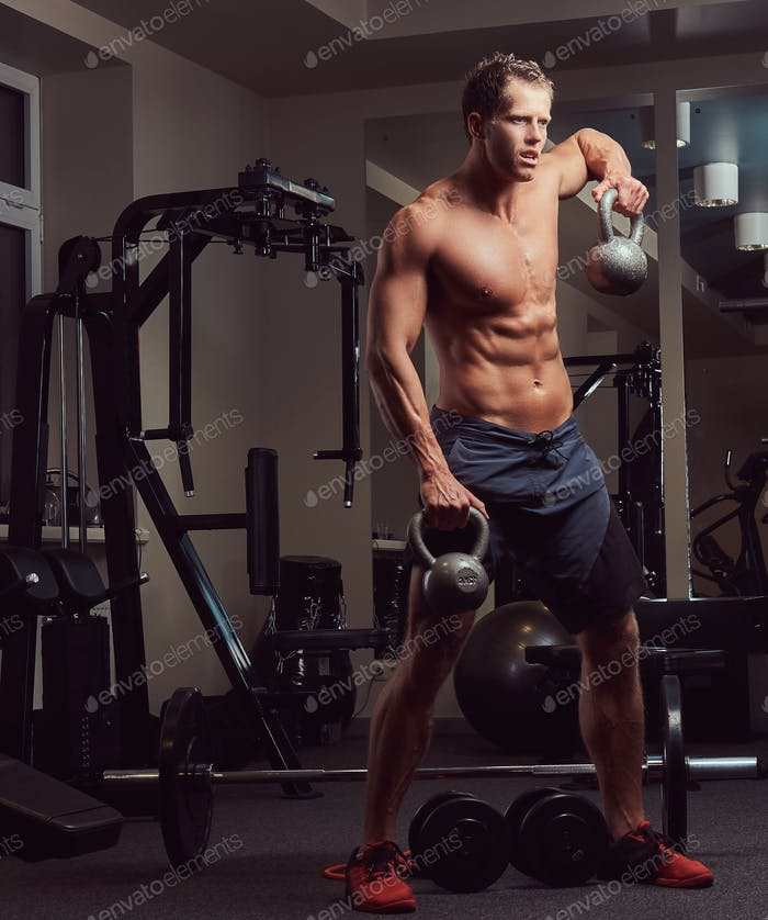Handsome muscular shirtless bodybuilder man doing exercises in the gym.