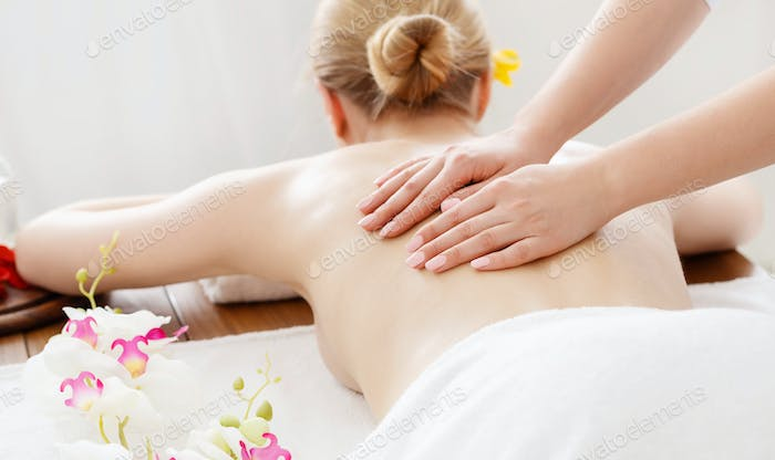 Relax and spa. Female hands on bare back girl on massage table