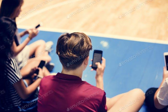 Gruppe von jungen Teenager-Freunden auf einem Basketballplatz entspannen und mit Smartphone