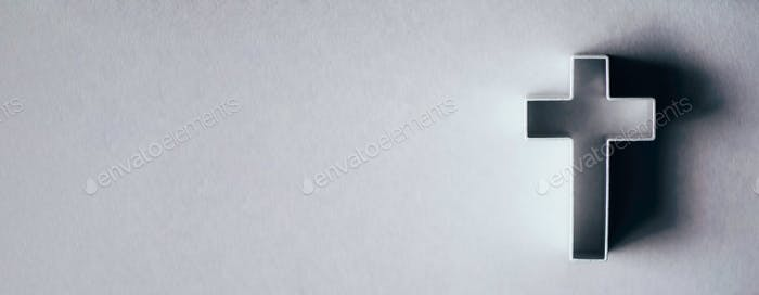 Silhouette of christian cross on grey background, soft bokeh lights background