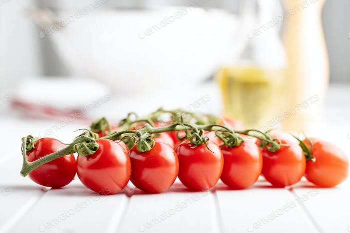 Fresh red cherry tomatoes. Small tomatoes on branch.