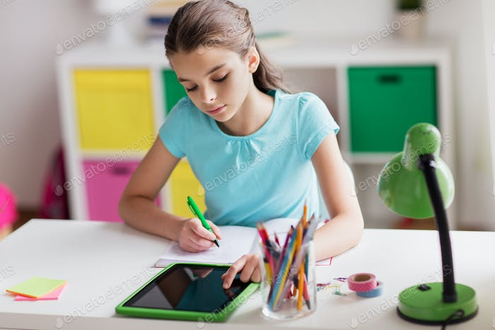 girl with tablet pc writing to notebook at home