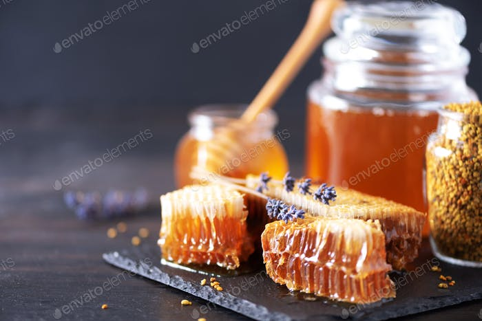 Bee pollen granules, honey jar with wooden dropper, honeycomb on dark backdrop. Copy space. Autumn
