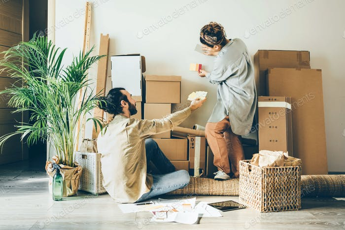 man and woman wearing casual apparel choose best color for new spacious apartment