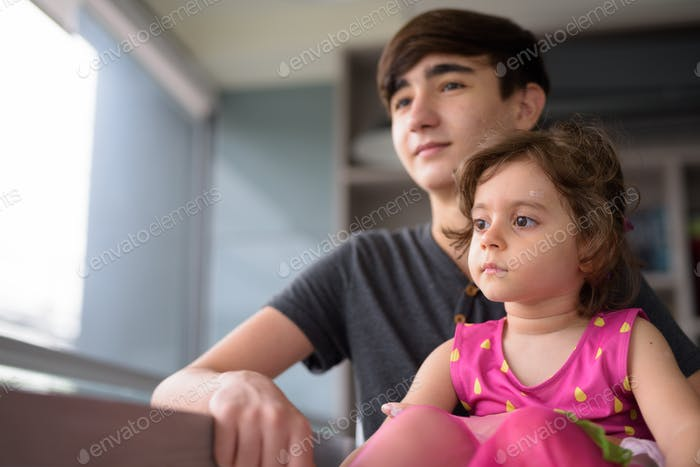 Young handsome Iranian teenage boy with little sister relaxing at home