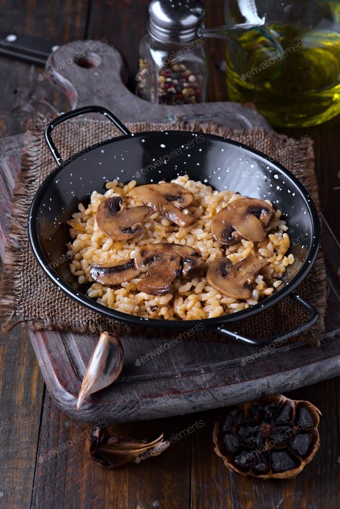 Portion von Reis mit Pilzen in Metallpfanne auf Holz