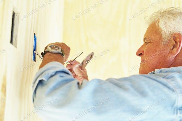Senior Mann, der an der elektrischen Verkabelung in einem Haus arbeitet.