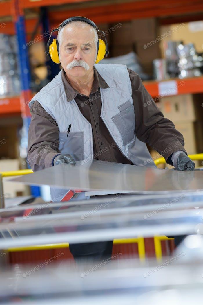 Senior man working wearing earmuffs