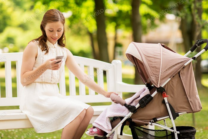 happy mother with smartphone and stroller at park