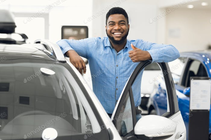 African Man Gesturing Thumbs-Up Approving Automobile After Test-Drive In Dealership