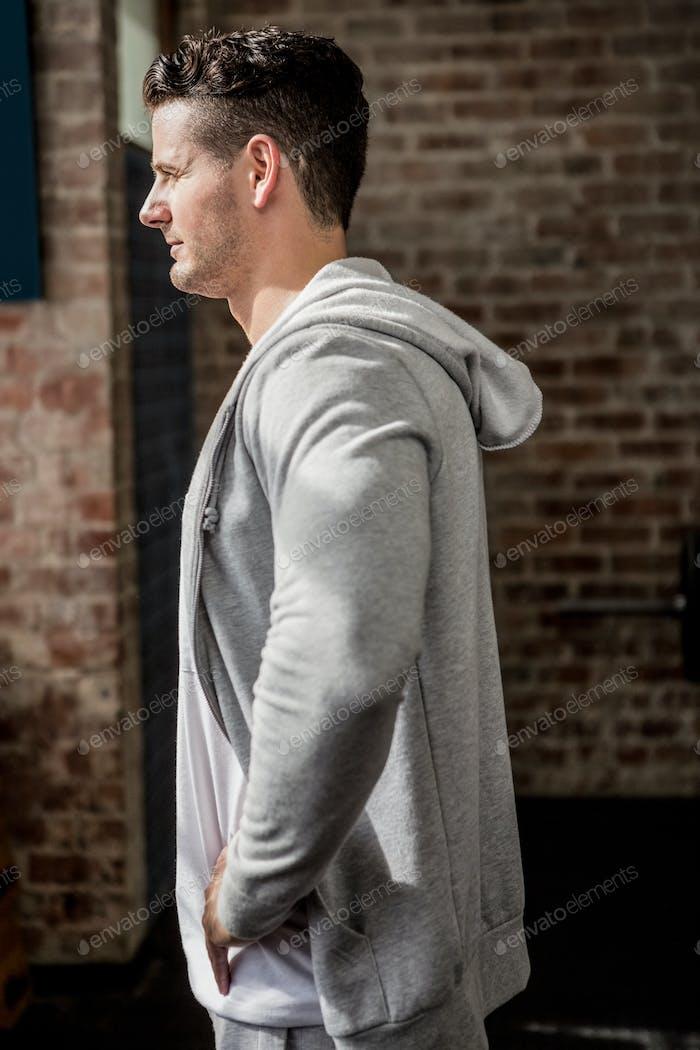 Side view of man wearing hood at gym