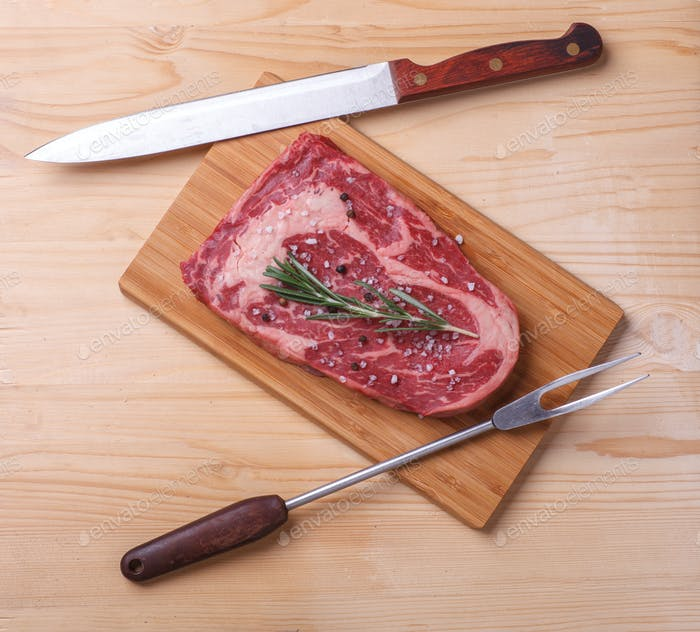 raw uncooked marble beef steak ribeye with knife and cook fork