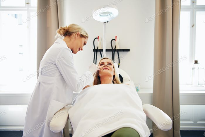 Doctor performing botox injections on a mature client's face