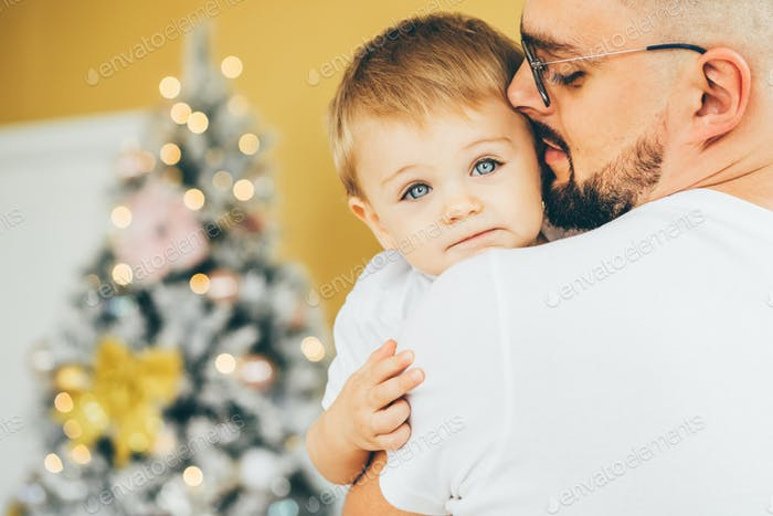 Close up father holding his son near the Christmas tree.