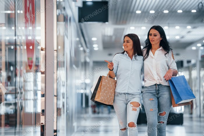 Two young women have a shopping day together in the supermarket