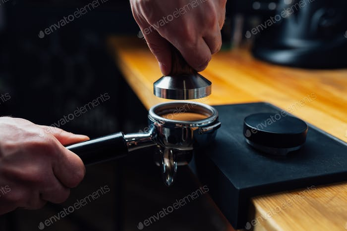 tempered coffee in portafilter on a dark background