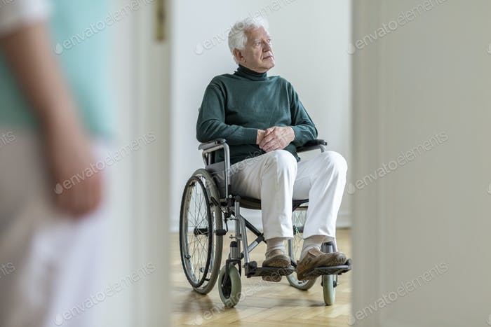 Sad disabled elderly man in a wheelchair in the hospital. Blurre