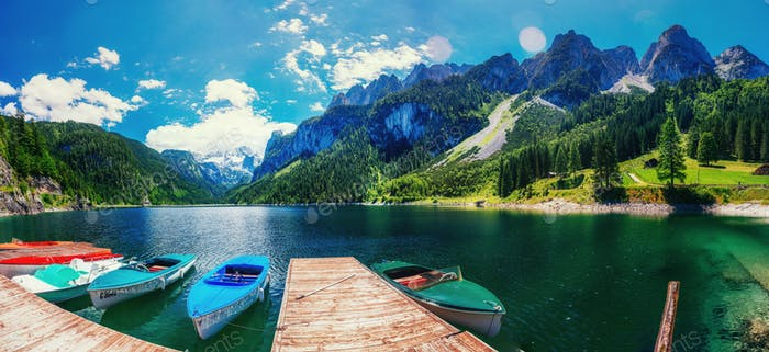 Boat on the pier at the lake surrounded by mountains. Italy. Eur