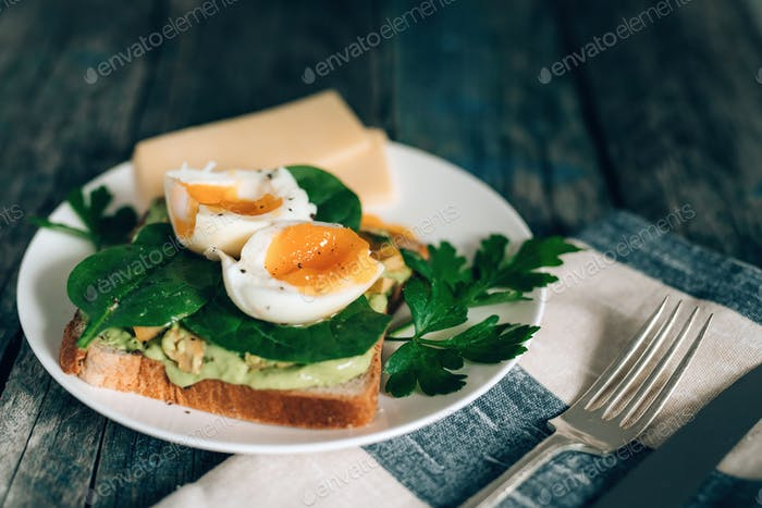Toast with avocado, boiled egg spinach and parsley on white plate