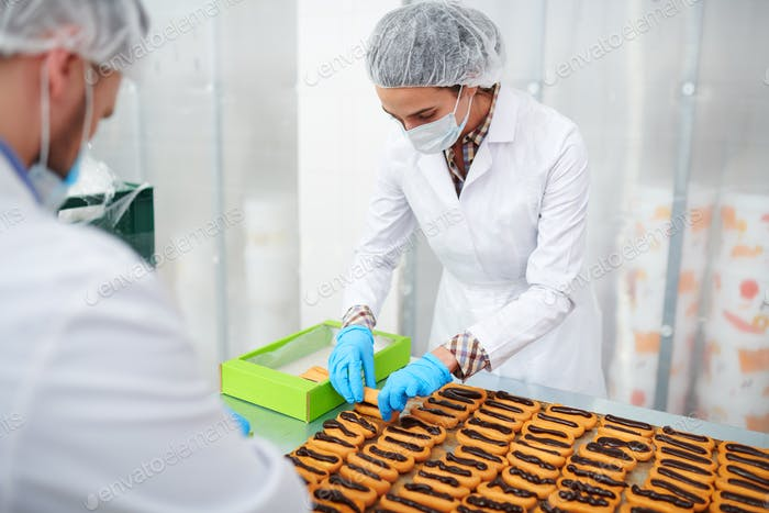 Confectionery factory employees packing ready pastry