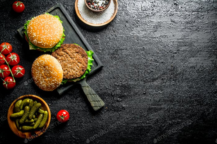 Burgers on a cutting Board with gherkins and spices in bowls.