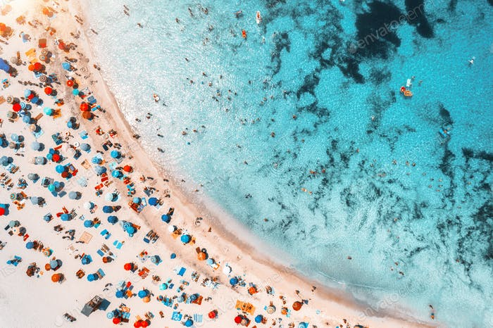 Luftaufnahme von Sandstrand mit Sonnenschirmen und Meer bei Sonnenuntergang