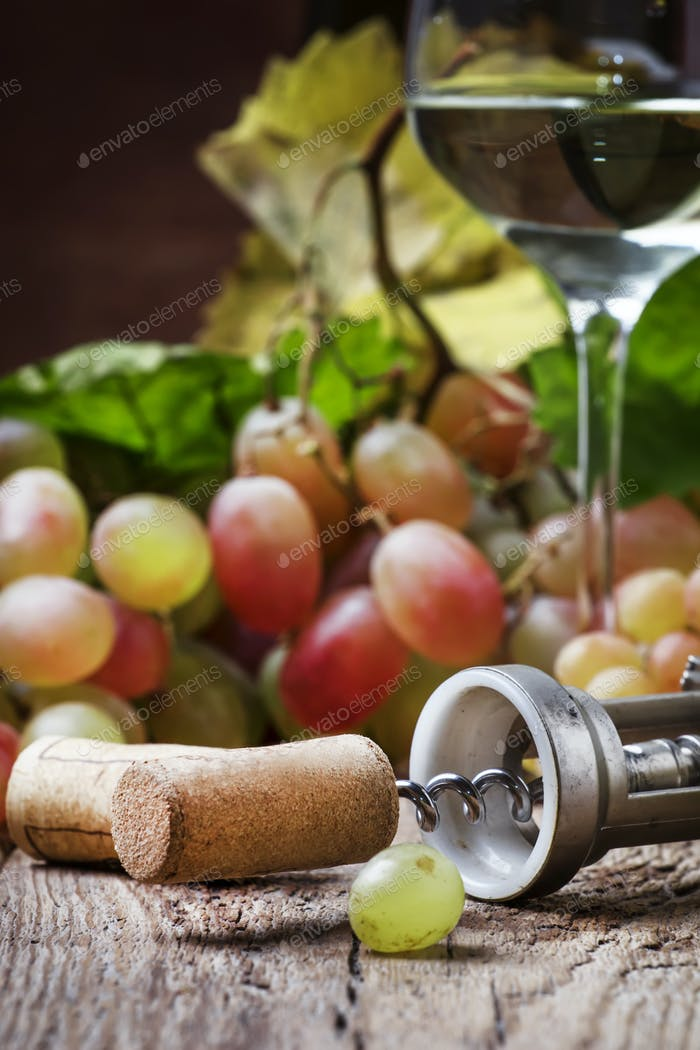 White wine in a glass, grapes, cork on a corkscrew