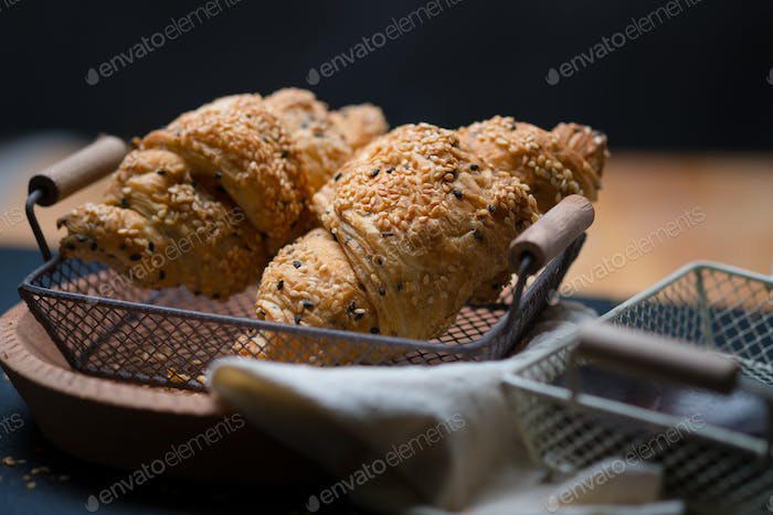 Sesame seed croissants in wire basket