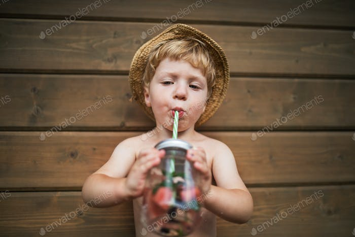 A small boy with a drink standing against wooden background on a patio in summer.