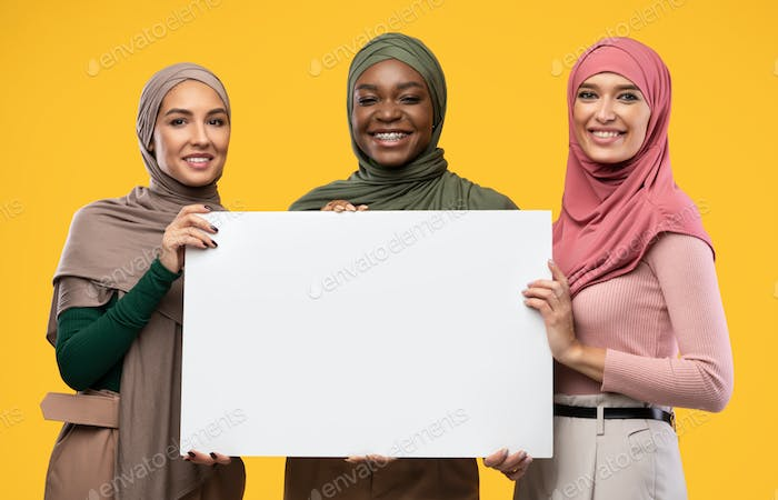 Three Muslim Women Holding Empty Poster Standing Over Yellow Background