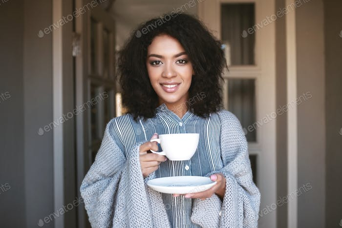 Young African American girl wrapped in plaid  with cup