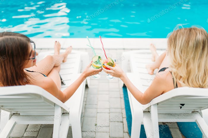 Two sexy girls relax with cocktails on deck chairs