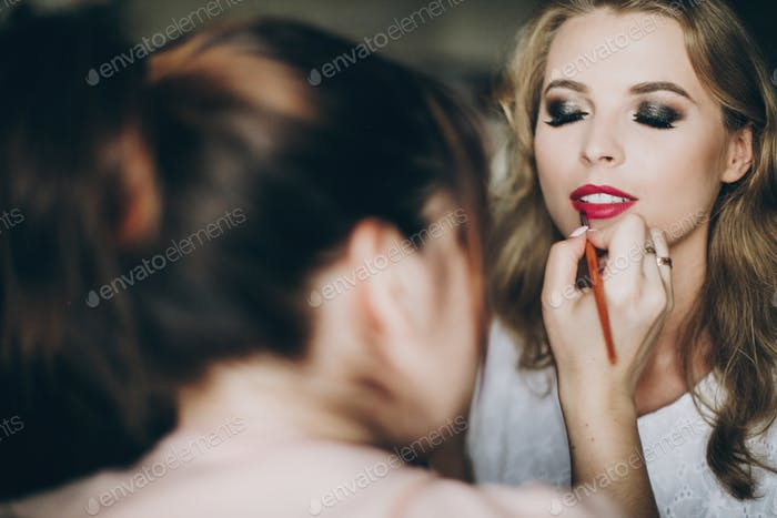 Beautiful happy bride getting her makeup done by professional make up artist
