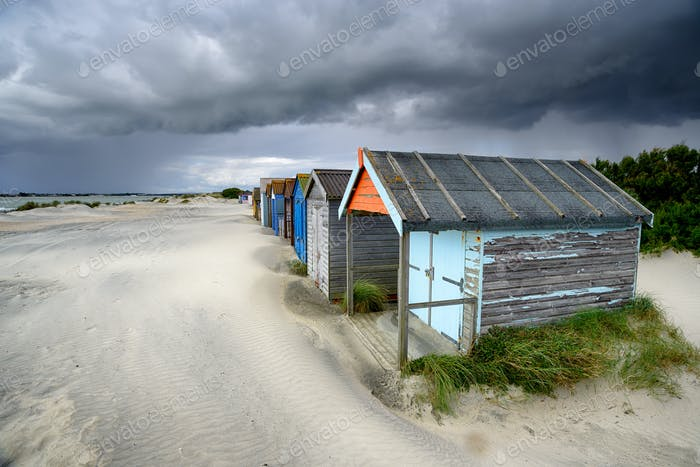 Beach Huts Under A Stormy Sky