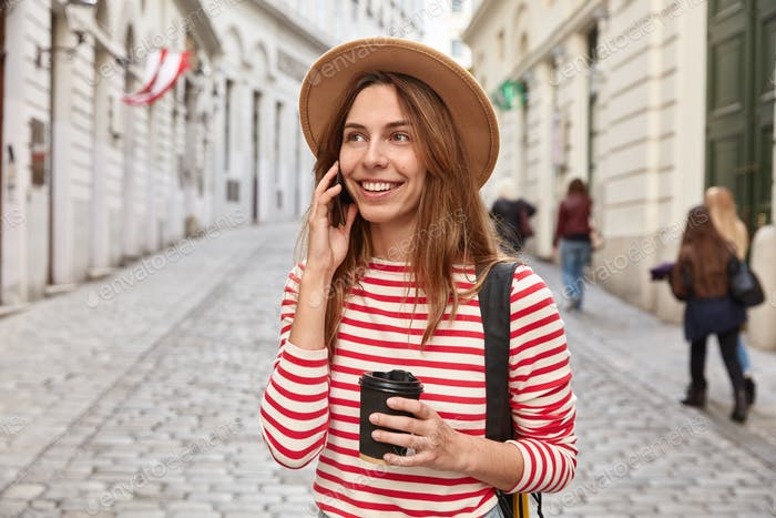 Gorgeous smiling tourist strolls around city, has phone conversation, holds takeaway coffee, focused