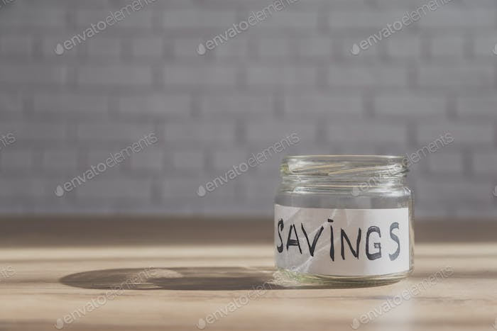 Empty jar for saving on table with copy space in background.