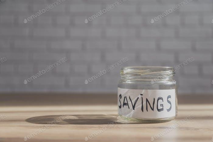 Leeres Glas zum Speichern auf dem Tisch mit Kopierraum im Hintergrund.
