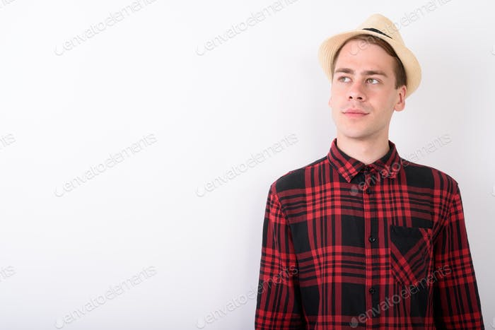 Young handsome tourist man wearing hat against white background