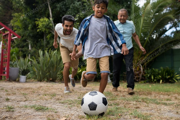 Happy family playing soccer in yard