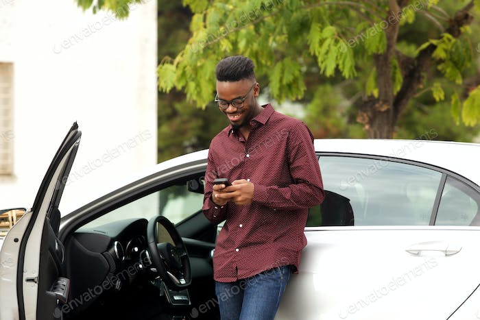 happy young man standing by his car with cellphone