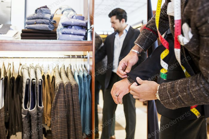 Tailor helping customer in clothing store