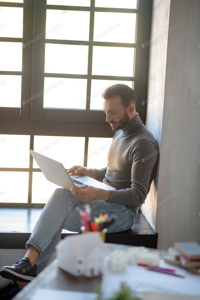 Bearded man working on laptop while having deadline