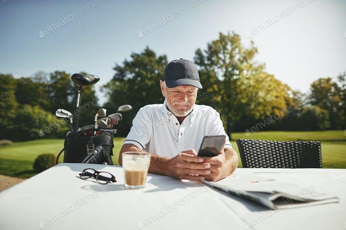 Senior man using a cellphone at his golf club restaurant