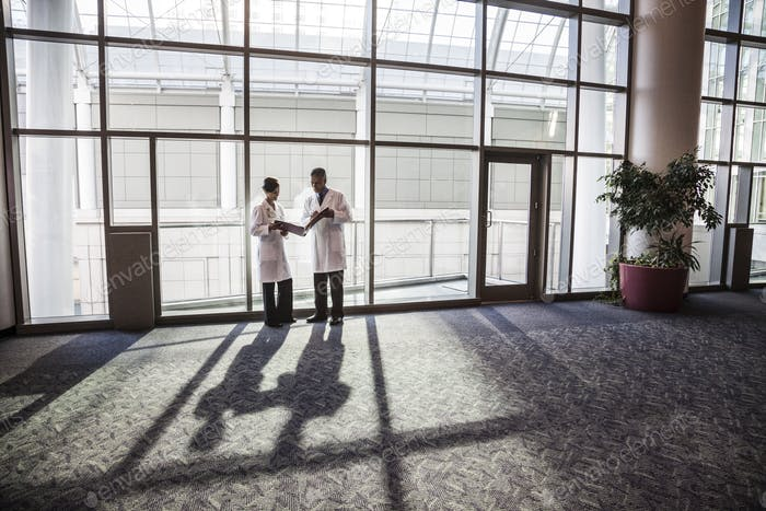 Man and woman doctors conferring over medical records in a hospital lobby.