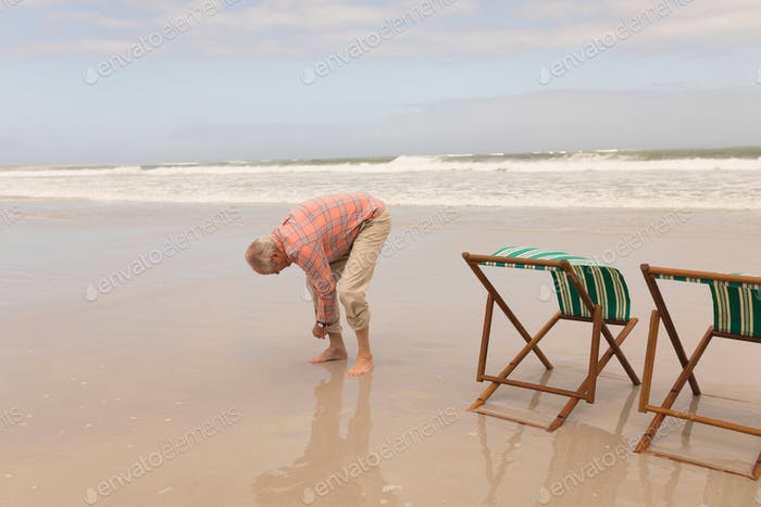 Relaxed senior man rolling up trousers on the beach with with sun loungers