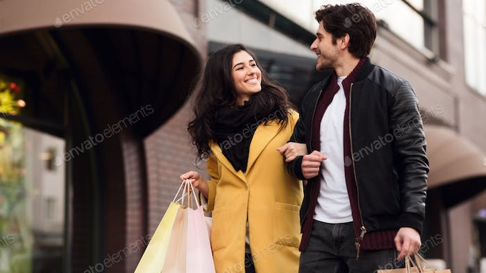 Loving couple walking with shopping bags at weekend