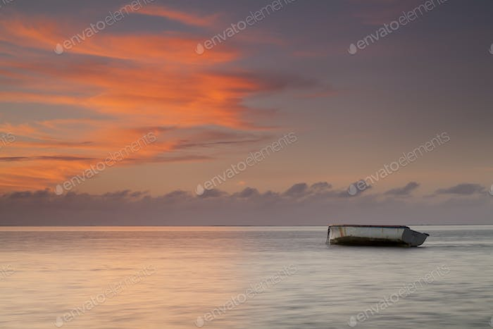 Sunrise on ocean beach with boat