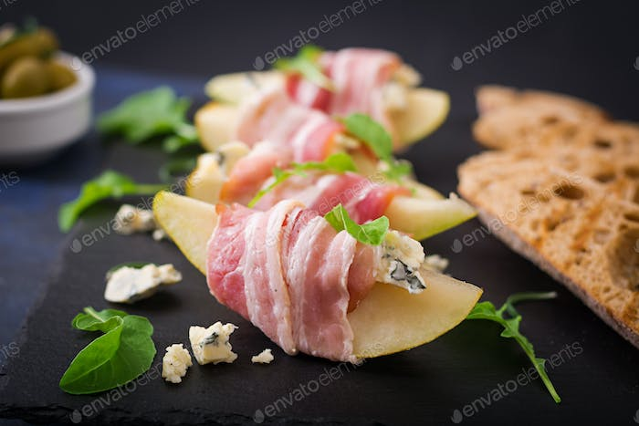 Appetizer with pear, blue cheese, prosciutto ham and toast for holidays on a dark plate.