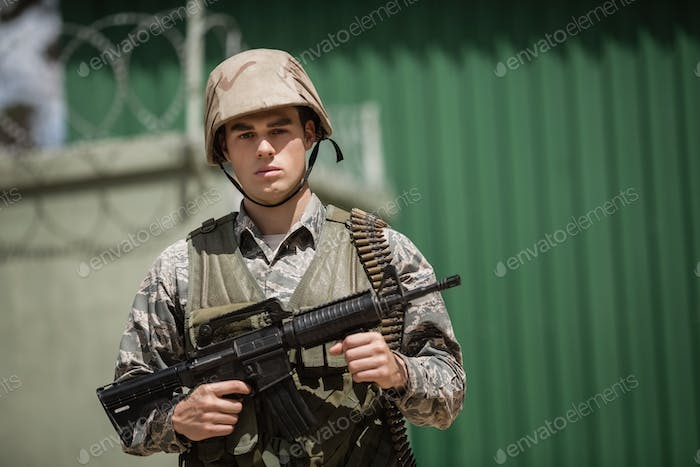 Portrait of military soldier standing with a rile