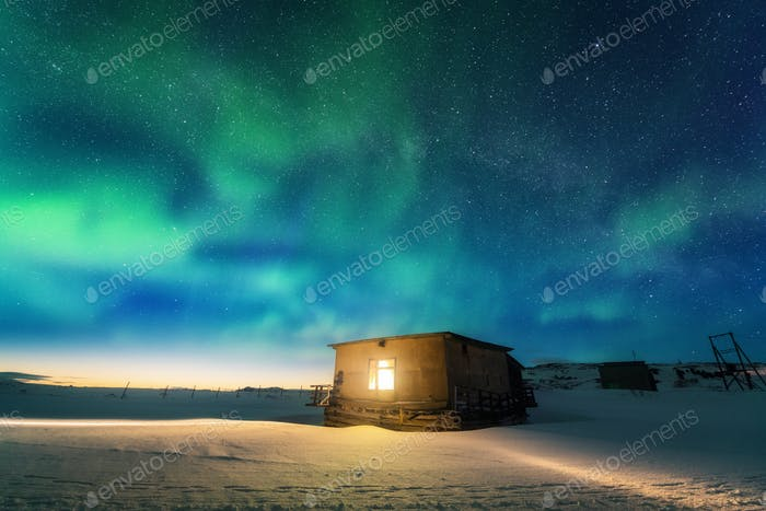 Aurora borealis over old small house with yellow light in window